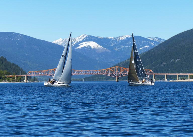 Two sailboat sailing towards Nelson's Big Orange Bridge