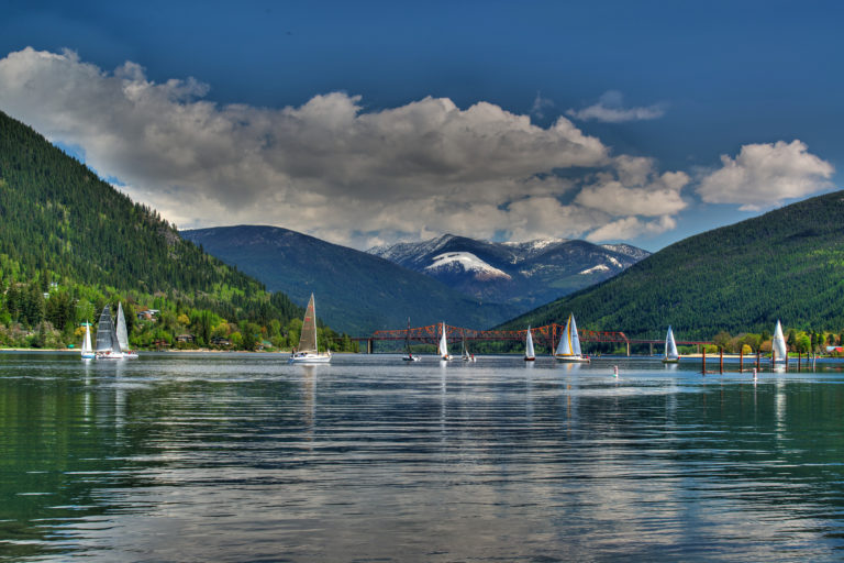 A group of sailboats in front of the Big Orange Bridge in Nelson, BC.